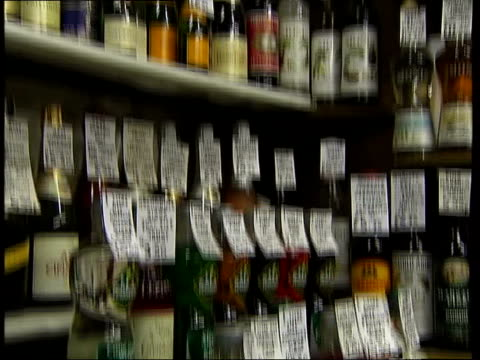 late night drinking blamed for rise in assaults; crime figures on website gv bottles of alcohol on shelf in shop tilt down sign ' extremely dangerous... - absinth stock-videos und b-roll-filmmaterial