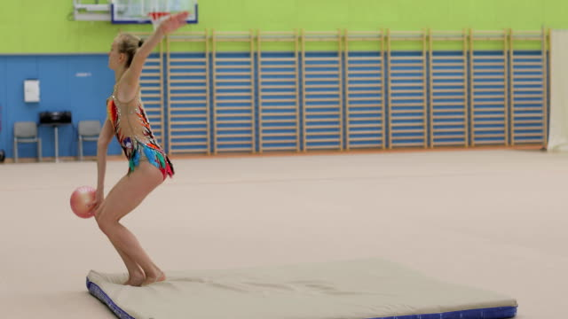 Late Teen Rhythmic Gymnastics Athlete Practicing with Ball