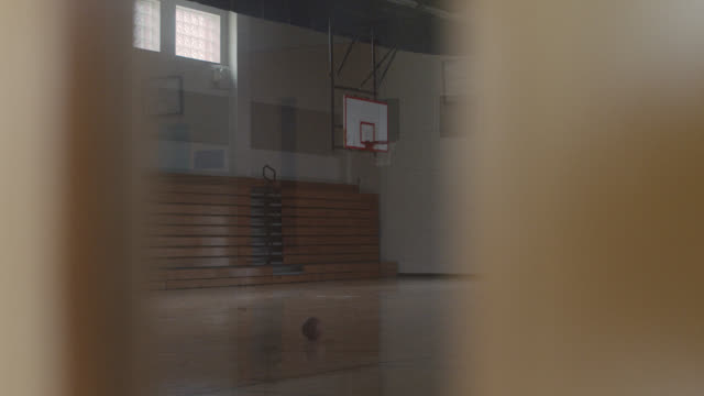 vídeos de stock, filmes e b-roll de lateral tracking shot of an empty basketball gym. - quadra esportiva