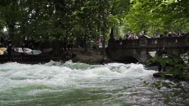 lateral view river surfing with bridge above - munich, germany - bach stock-videos und b-roll-filmmaterial