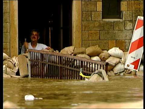 latest itn germany dresden lms man waving from doorway surrounded by sandbags as flood water in street in f/g tlms tops of road signs just above... - 2002 stock-videos und b-roll-filmmaterial