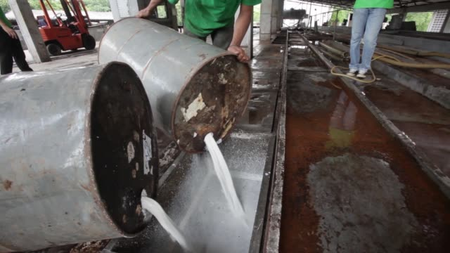 latex flows from containers into channels at the thai hua rubber pcl factory in samnuktong rayong province workers pour latex fluid from barrels into... - latex stock videos & royalty-free footage