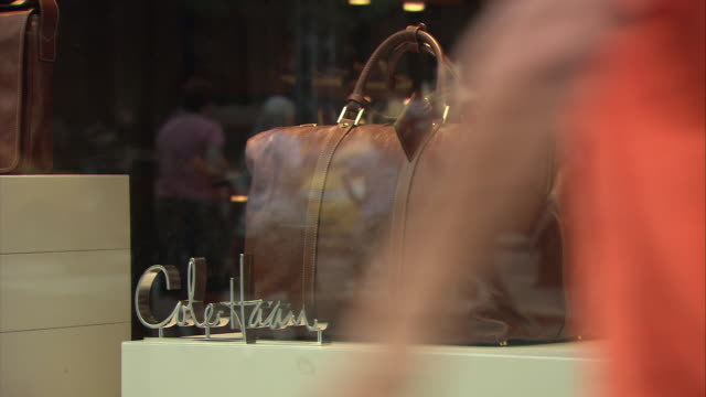 cu lather handbag on window display at cole haan store, 620 5th avenue, reflection of shoppers and nyc street traffic in window / manhattan, new york city, new york, usa - espositore per negozio video stock e b–roll