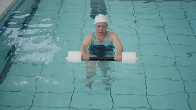 vídeos de stock, filmes e b-roll de mulher adulta latino-americana fazendo exercícios de fisioterapia na água - physical injury