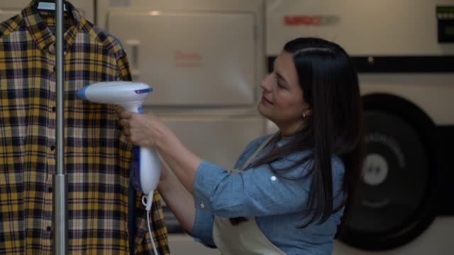 vidéos et rushes de amérique latine adulte travaillant dans un service de blanchisserie, éliminer les plis de la chemise avec un défroisseur - fer