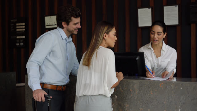 vídeos de stock e filmes b-roll de latin american beautiful business couple signing a form checking into hotel and friendly receptionist helping them - rececionista