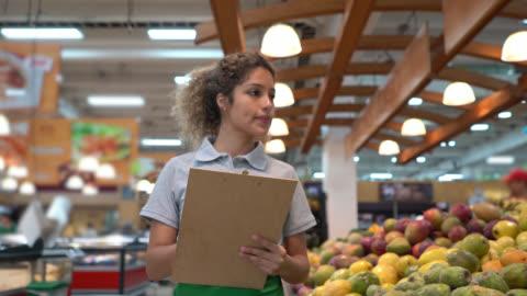 vídeos y material grabado en eventos de stock de hermosa vendedora latinoamericana comprobando la exhibición de venta al por menor de frutas y el inventario en el portapapeles - hispanoamérica