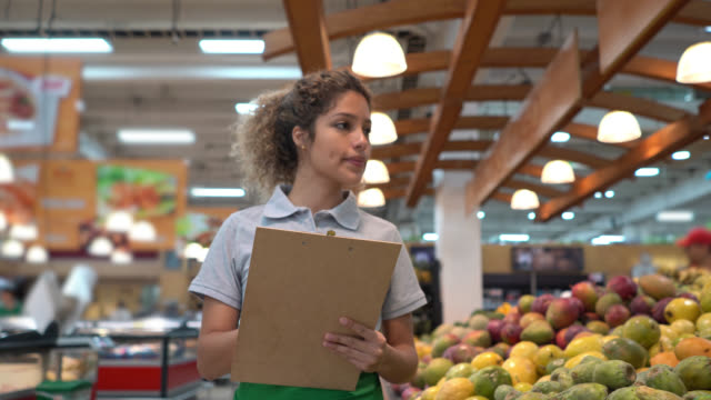 latin american beautiful saleswoman checking the fruit retail display and inventory on clipboard - latin american and hispanic stock videos & royalty-free footage