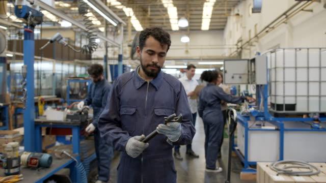 vidéos et rushes de travailleur bleu d'amérique latine retenant une clé souriant à l'appareil-photo dans une usine de pompe à eau de fabrication - tenir