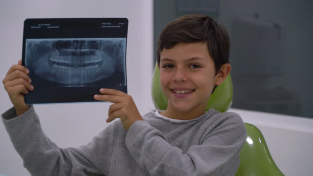 latin american boy holding an xray of his teeth smiling at camera while sitting on dentist chair - dental hygiene stock videos & royalty-free footage