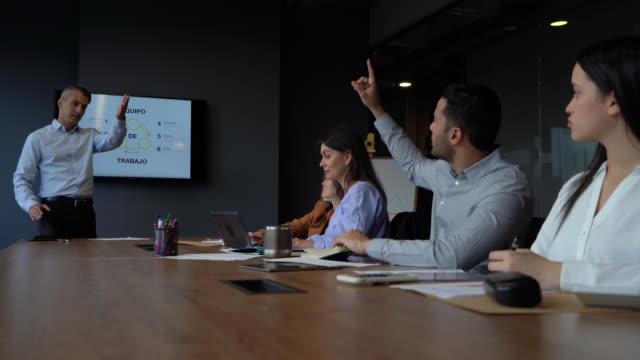 vídeos y material grabado en eventos de stock de hombre de negocios latinoamericano respondiendo preguntas a colegas durante una presentación en la sala de conferencias - preguntar