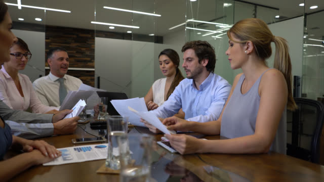 Latin American business man leading a meeting asking questions to partners while they all hold some documents