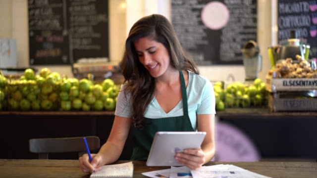 Latin american business owner of a juice bar doing the books using a computer tablet and writing on a notepad