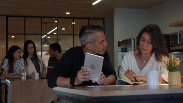latin american business partners planning something while taking notes and using a tablet at a coworking office - casual clothing stock videos & royalty-free footage