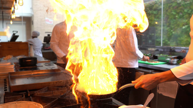 latin american chef cooking flambe while the team is preparing other things - chef stock videos & royalty-free footage