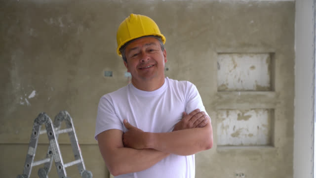 vídeos de stock e filmes b-roll de latin american contractor at an apartment doing a renovation smiling at camera with arms crossed - latin american and hispanic ethnicity