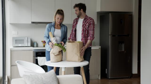 vídeos de stock e filmes b-roll de latin american couple arriving home after grocery shopping talking and smiling - saco de compras