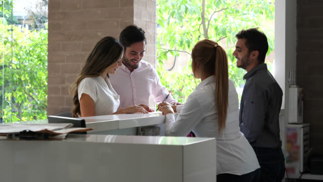 Latin American couple arriving to the hotel at the front desk talking to manager and receptionist