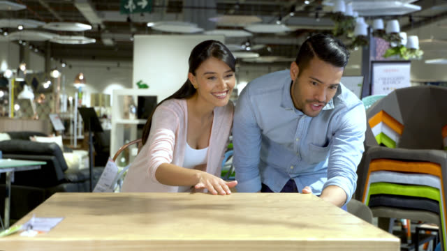 latin american couple at a furniture store looking at a wooden dining table very happy - dining table stock videos & royalty-free footage