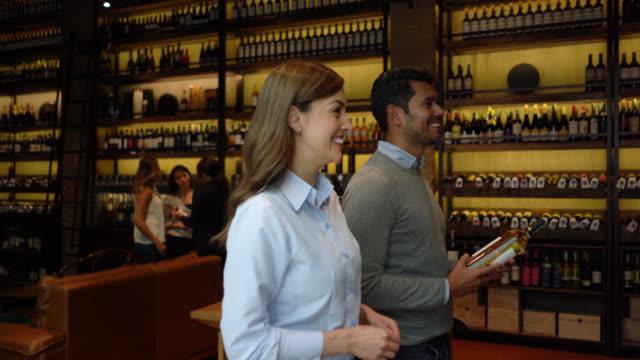 ワインテイスティングセラーのラテンアメリカのカップルがチェックアウトし、男性のレジにボトルを渡すために歩いて - ワインバー点の映像素材/bロール