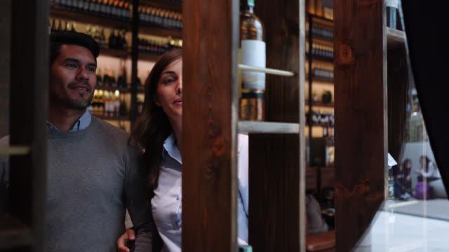 ラテンアメリカのカップルは、ディスプレイの話と笑顔からワインボトルをつかむ - ワインバー点の映像素材/bロール