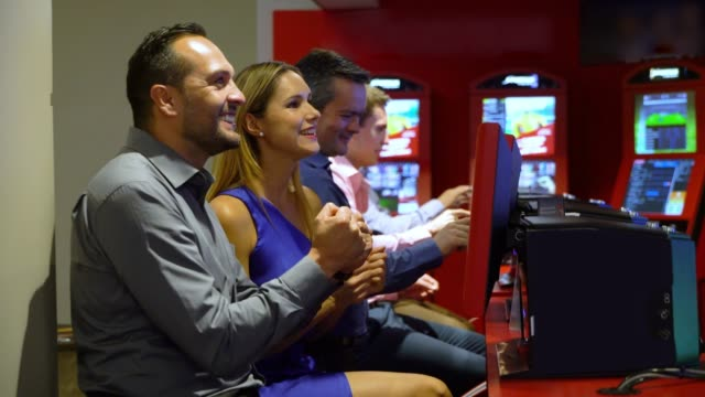 latin american couple having fun at the casino sports betting and celebrating - gambling stock videos & royalty-free footage