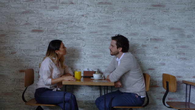 latin american couple on a date at a bakery enjoying juice and coffee talking while waitress brings a croissant - french food stock videos & royalty-free footage