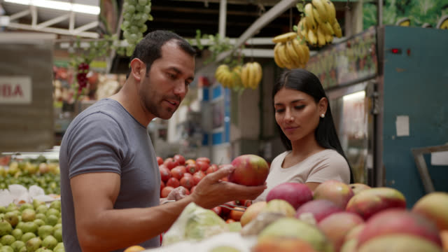 latin american couple shopping for fruit at a farmer's market talking and smiling - market trader stock videos & royalty-free footage