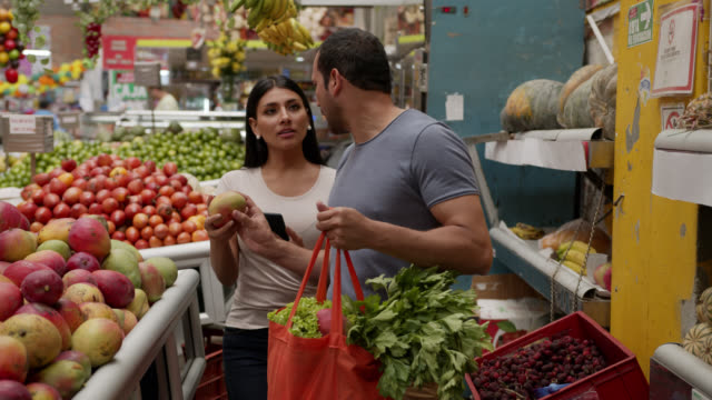 latin american couple shopping for fruits and vegetables using a list on smartphone while man adds everything to a reusable bag - market trader stock videos & royalty-free footage