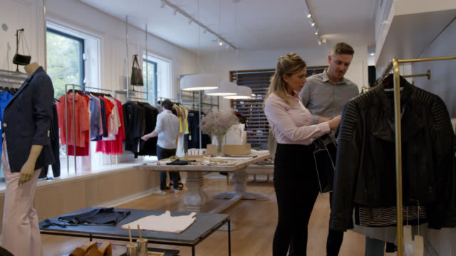 latin american couple shopping together looking at a sweater while talking at a women's boutique - clothes rail stock videos & royalty-free footage