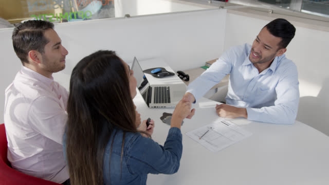 latin american couple signing a form at a car dealership and handshaking with friendly salesman - car showroom stock videos & royalty-free footage