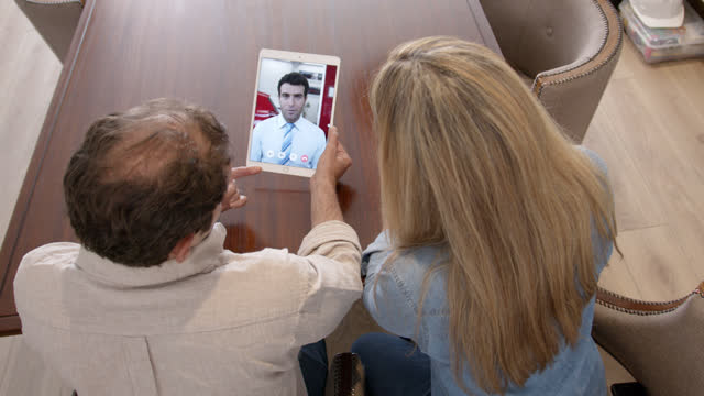 latin american couple talking with friendly car salesman on a video call from their home - sale stock videos & royalty-free footage