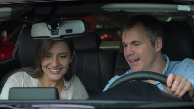 Latin american couple test driving a car they are looking to buy