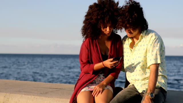 latin american couple using smart phone by the sea - cuba stock videos & royalty-free footage