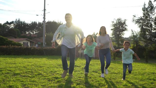 stockvideo's en b-roll-footage met latijns-amerikaanse paar met hun twee kinderen die handen vasthouden en rennen in hun achtertuin erg blij - latin american and hispanic ethnicity