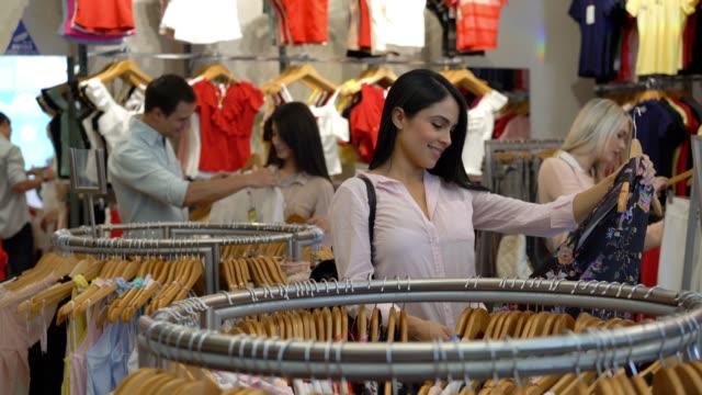 vídeos de stock e filmes b-roll de latin american customers at a clothing store choosing from clothing rack looking very happy - viciado em compras