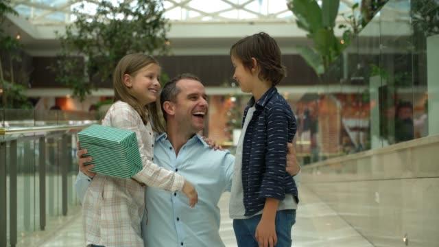 vídeos y material grabado en eventos de stock de la hija y el hijo de américa latina sorprenden a su padre en el centro comercial con un regalo para el día del padre - father day