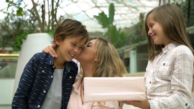 vídeos de stock, filmes e b-roll de latin-a filha e o filho bonitos americanos surpreendem sua mamã na alameda com um presente para o dia de matriz - mãos cobrindo olhos