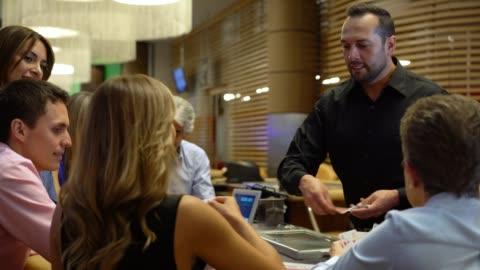 latein-amerikanischen händler auf die black-jack tisch ausgeteilten karten zu einer gruppe von menschen in einem casino - poker stock-videos und b-roll-filmmaterial