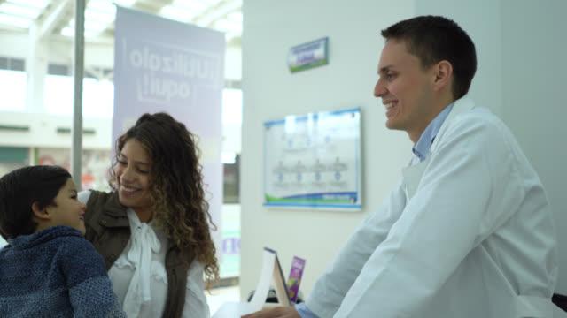 stockvideo's en b-roll-footage met latijns-amerikaanse tandarts groet een moeder die haar zoon draagt in zijn praktijk - latin american and hispanic ethnicity