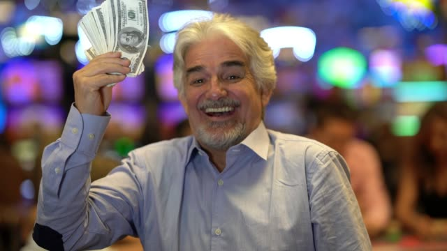latin american elder man holding a bunch of money while looking and laughing to camera at the casino - casinò video stock e b–roll