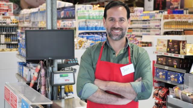 vídeos de stock e filmes b-roll de latin american employee , essential worker, cashier in supermarket during pandemic coronavirus - serviços essenciais