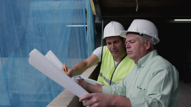 latin american engineer and architect working together at a construction site checking a blueprint while talking - inspector stock videos & royalty-free footage