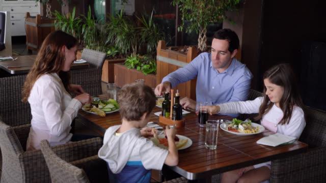vídeos de stock e filmes b-roll de latin american family at a restaurant hotel enjoying a delicious breakfast - restaurante