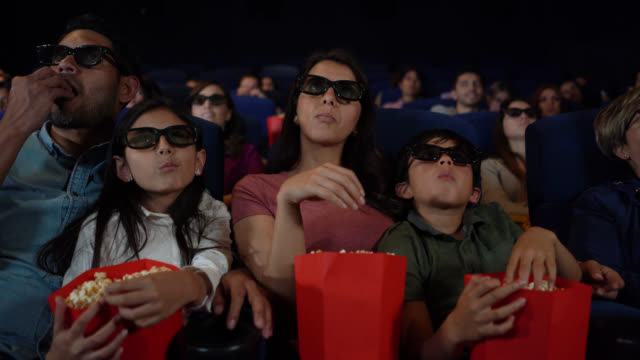Latin american family enjoying a 3D movie while eating snacks looking very engaged