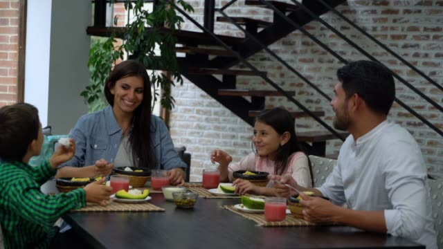stockvideo's en b-roll-footage met latijns-amerikaanse familie genieten van een traditionele ajiaco tijdens het praten en glimlachen - latin american and hispanic ethnicity