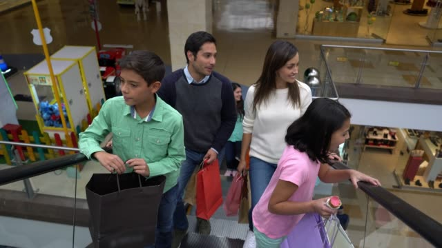 latin american family going up the escalators at the mall talking and each carrying their bags - shopping centre stock videos & royalty-free footage