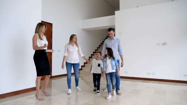 latin american family looking at a property with a real estate agent father pointing at something and kids looking very excited - showing stock videos and b-roll footage