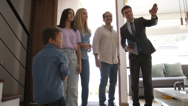 latin american family with two children and a real estate agent showing them a beautiful property all looking very excited - salesman stock videos & royalty-free footage