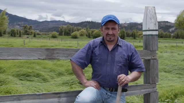 vídeos de stock, filmes e b-roll de trabalhador rural latino-americano inclinando um pé em uma cerca de madeira de frente para a câmera sorrindo - cerca